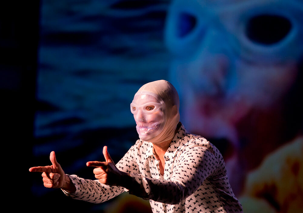 Endurance swimmer Diana Nyad wears a jellyfish mask Thursday, Feb. 19, 2015, as she performs her one-woman play that portrays her 111-mile swim from Cuba to Key West in a Key West, Fla., theater near the beach where she concluded the record-setting athletic feat in September 2013.