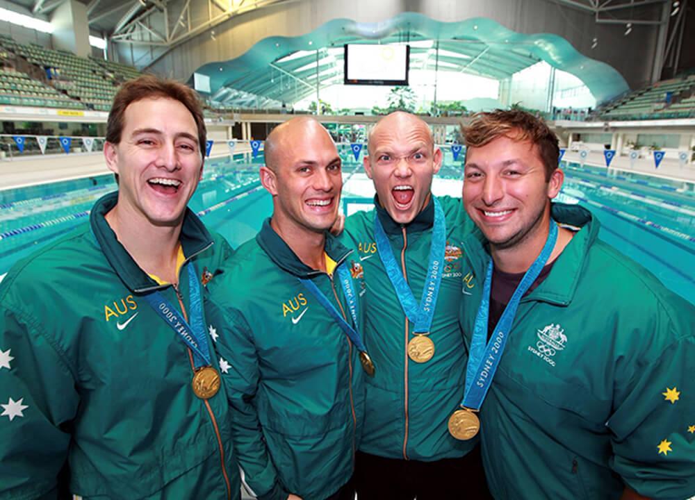 Swimming World March 2020 - Takeoff To Tokyo Series - Air-Guitar Race - 2000 Olympics - AUS 400 FR Gold Medal Team - fydler, callus, klim, thorpe - Sydney 2000
