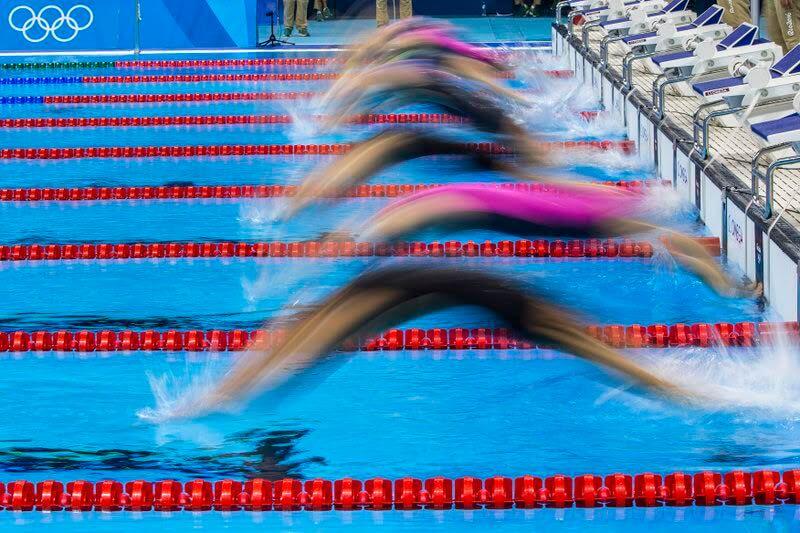 Swimmer start for the Backstroke leg in the women's 4x100m Medley Relay Heat 2