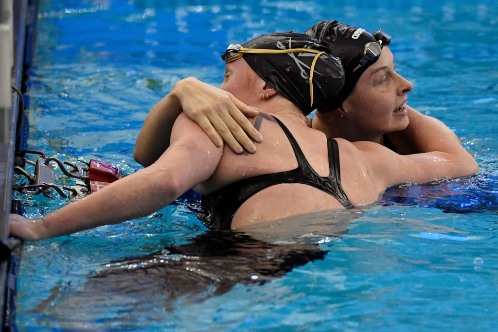 GREENSBORO, NORTH CAROLINA - MARCH 20: Sophie Hansson of the NC State Wolfpack hugs Ella Nelson of the Virginia Cavaliers after winning the 200 Yard Breaststroke during the Division I Women's Swimming & Diving Championships held at the Greensboro Aquatic Center on March 20, 2021 in Greensboro, North Carolina. (Photo by Mike Comer/NCAA Photos via Getty Images)