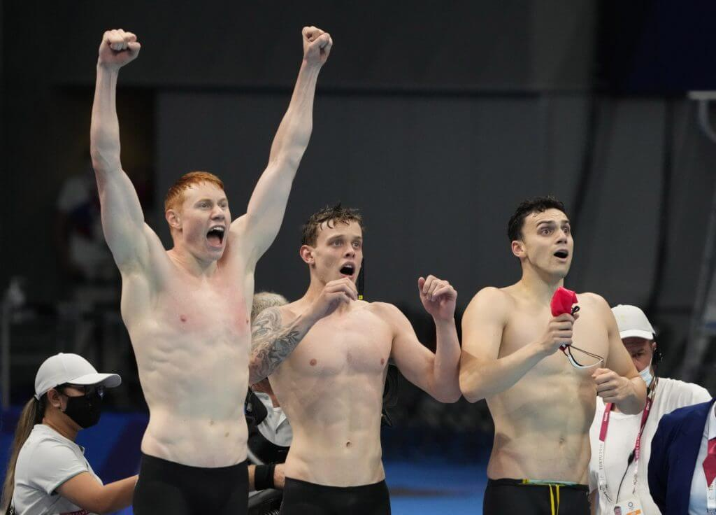 Jul 28, 2021; Tokyo, Japan; Tom Dean (GBR), James Guy (GBR) and Matthew Richards (GBR) celebrate as Great Britain wins the men's 4x200m freestyle relay during the Tokyo 2020 Olympic Summer Games at Tokyo Aquatics Centre. Mandatory Credit: Rob Schumacher-USA TODAY Sports
