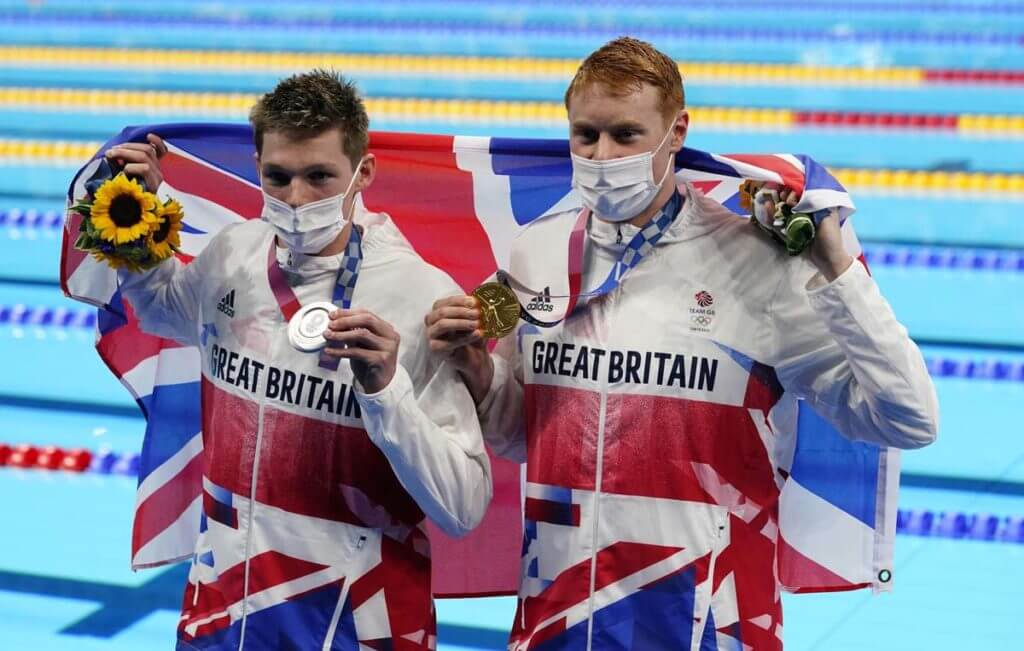 Jul 27, 2021; Tokyo, Japan; Tom Dean (GBR) and Duncan Scott (GBR) celebrate with their medals during the medals ceremony for the men's 200m freestyle during the Tokyo 2020 Olympic Summer Games at Tokyo Aquatics Centre. Mandatory Credit: Rob Schumacher-USA TODAY Sports; olympics