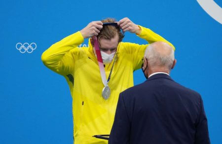 Jul 25, 2021; Tokyo, Japan; Jack McLoughlin (AUS) puts on his silver medal during the medals ceremony for the men's 400m freestyle during the Tokyo 2020 Olympic Summer Games at Tokyo Aquatics Centre. Mandatory Credit: Robert Hanashiro-USA TODAY Network