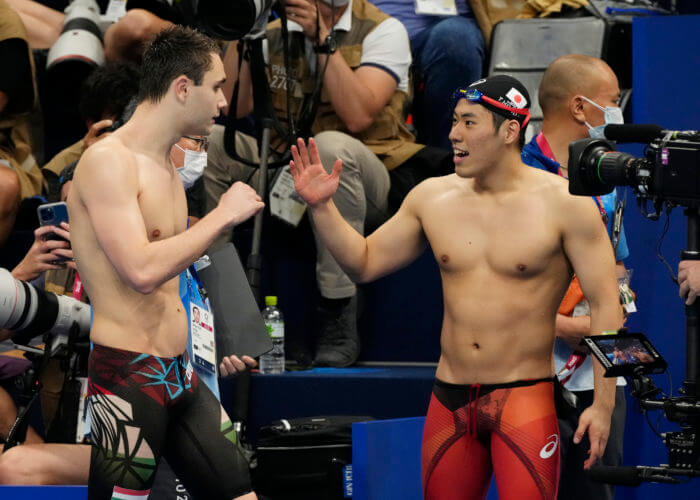 Jul 28, 2021; Tokyo, Japan; Kristof Milak (HUN) and Tomaru Honda (JPN) celebrate after placing first and second in the men's 200m butterfly final during the Tokyo 2020 Olympic Summer Games at Tokyo Aquatics Centre. Mandatory Credit: Rob Schumacher-USA TODAY Sports