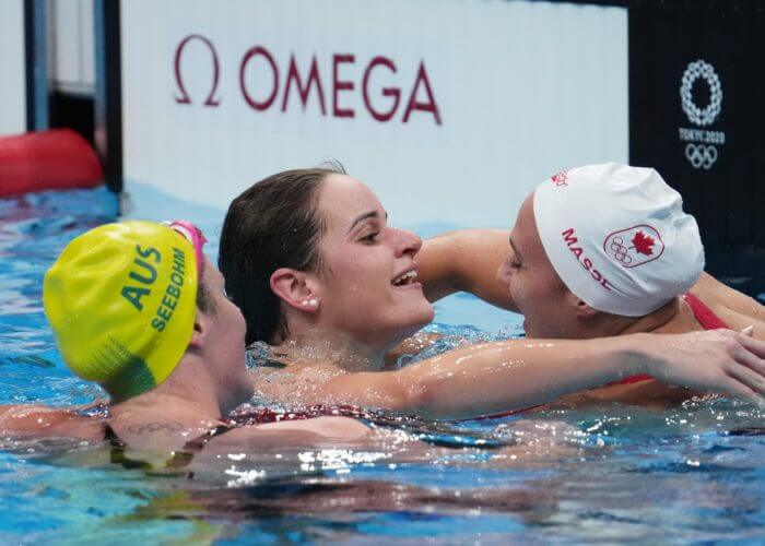 Jul 27, 2021; Tokyo, Japan; Kaylee McKeown (AUS), center, is congratulated by Kylie Masse (CAN)after placing first and second in the women's 100m backstroke final during the Tokyo 2020 Olympic Summer Games at Tokyo Aquatics Centre. Mandatory Credit: Robert Hanashiro-USA TODAY Sports